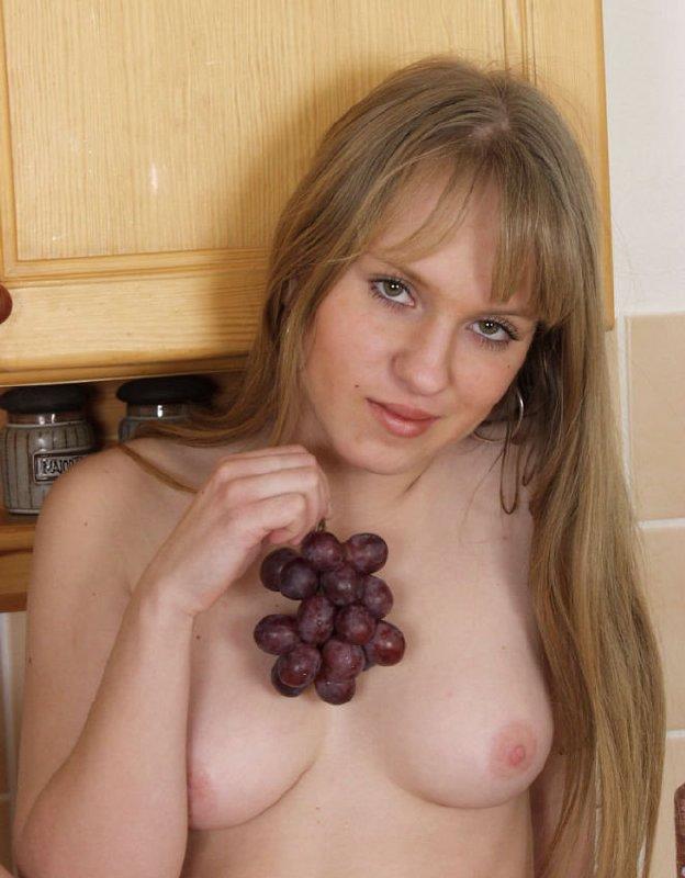 Jovencita comiendo las uvas en la cocina