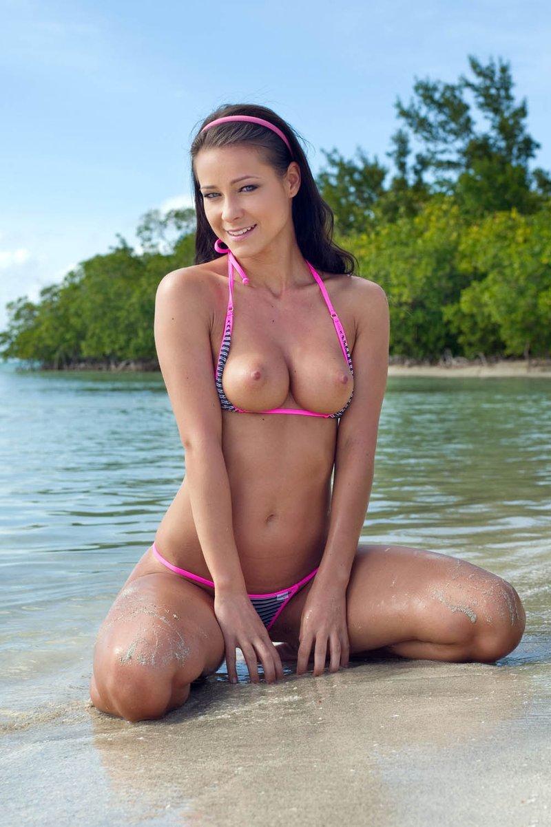Nena posando desnuda en la playa
