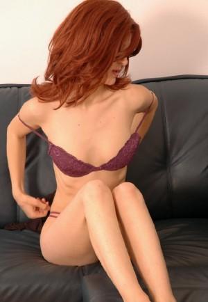 Colegiala pelirroja desnuda en el sofa